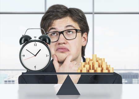 streamlining: Pondering businessman about the balance between time and money. On the one side is money, on the other one is an alarm clock. The concept of time is money. An office with New York panoramic view. Stock Photo