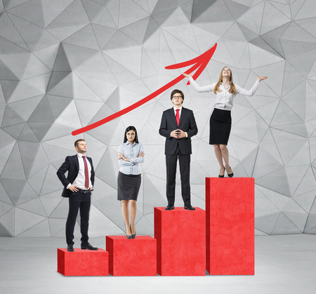 corporate ladder: Stairs as a huge red bar chart are in the room with concrete floor and contemporary wall. Business people are standing on each step as a concept of corporate ladder. A red arrow is on the wall. Stock Photo