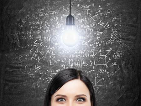 simbolos matematicos: A la frente de la mujer morena que está pensando en la solución del complicado problema matemático. Fórmulas matemáticas están en el pizarrón negro. Una bombilla de luz como un concepto de una solución. Acercan Analytics.