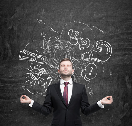 achiever: Meditative businessman is trying to find an approach to the new business idea. A sketch from business icons is drawn on the black chalkboard. The concept of brainstorm process. Stock Photo