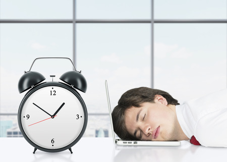 drowsiness: Relaxing professional on the laptop in the panoramic office. An alarm clock is on foreground. Stock Photo
