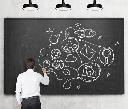 man rear view: Rear view of young man in formal clothes who is drawing connected business icons on the black chalkboard. The concept of a communication building a relationships. Stock Photo