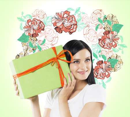 light green wall: A curious brunette woman tries to guess what is inside the green gift box. The sketch of colourful flowers is drawn on the light green wall.