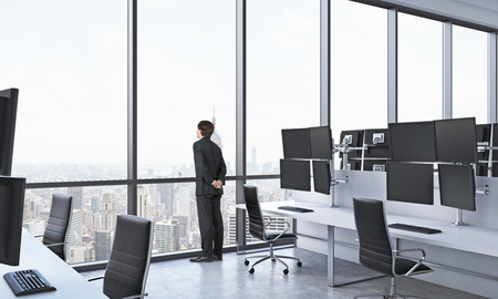 service broker: Rear view of a man in formal suit who is looking out the window in the modern panoramic office with New York view. White tables equipped with modern traders stations and black chairs. Stock Photo