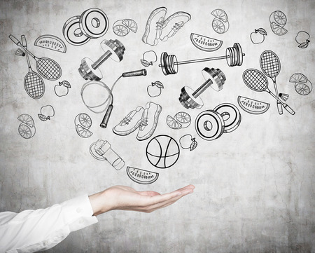 A mans hand in formal shirt offers a range of sport activities and sport equipment. Sport icons are drawn on the concrete wall. A concept of gym culture among office clerks.