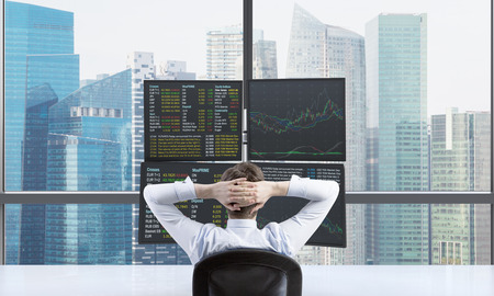 A rear view of relaxing trader who is waiting for a success of his position in front of trading station. Trading at forex market. Singapore panoramic view. Stock Photo