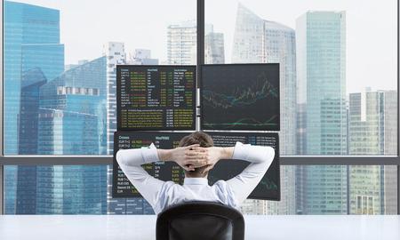 broker: Una vista posterior del operador que está esperando un éxito de su posición frente a la estación de comercio relajante. Negociaciones en el mercado de divisas. vista panorámica de Singapur. Foto de archivo