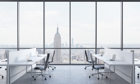 company premises: Workplaces in a bright modern open space office. White tables equipped with modern laptops and black chairs. New York in the panoramic windows. 3D rendering.