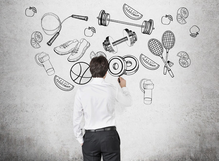 lifestyle: A rear view of a person in formal clothes who is drawing a range of sport activities and sport equipment on the concrete wall. A concept of gym culture among office clerks.