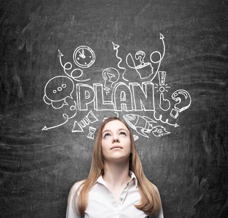 planificacion: Una joven de negocios pensativa está soñando sobre la construcción de un plan de negocios para el desarrollo empresarial. Esbozo de plan de negocios se dibuja en el pizarrón negro. Foto de archivo