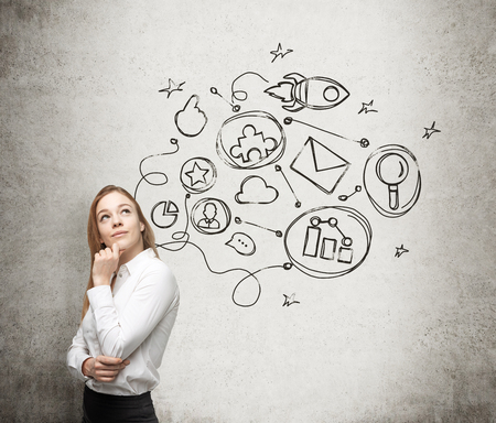 entrepreneurial: A young lady is thinking about an optimisation scheme in some business process. Some connected icons are drawn on the concrete wall.