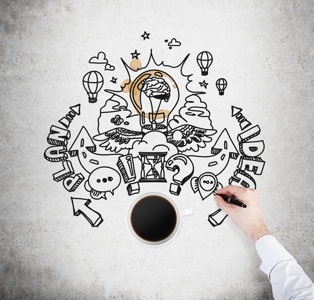 A top view of a cup of coffee and a hand which is drawing a sketch of developing a new business plan. A concrete surface as a background. A light bulb as a concept of brainstorm.