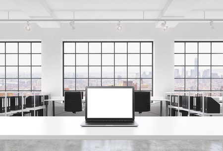docs: A workplace in a bright modern loft open space office. A working desk is equipped with a modern laptop with white copy space in the screen. Docs shelves. New York view in the windows. 3D rendering.