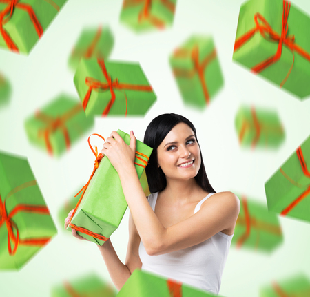 eagerness: A portrait of dreaming woman who imagines green gift boxes. Light green background. Stock Photo