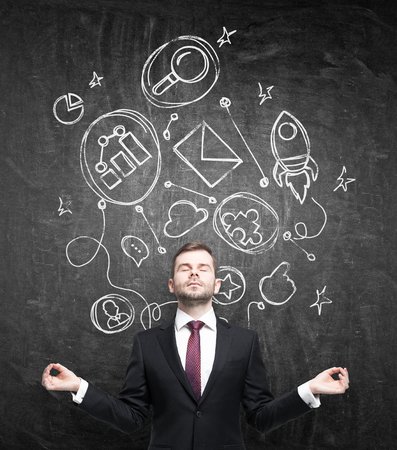 meditates: Meditative businessman in formal suit is thinking about building of some business relationships. Connected business icons are drawn on the black chalkboard.