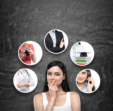 A portrait of a young artful brunette lady who is trying to chose the right career path. A range of images with different careers are drawn on the black chalkboard. Banque d'images