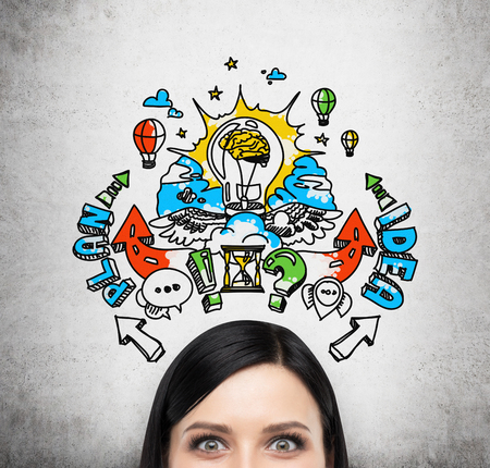 A forehead of brunette woman who is brainstorming about a business plan for business development. A colourful business plan sketch is drawn on the concrete wall behind the person. Stock Photo