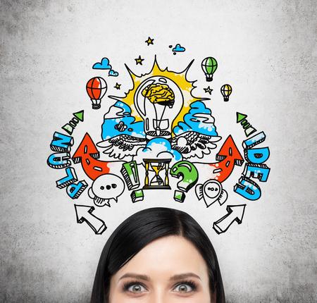 planificacion: A la frente de la mujer morena que se lluvia de ideas sobre un plan de negocios para el desarrollo empresarial. Un bosquejo del plan de negocios de colores se dibuja en la pared de cemento detrás de la persona.
