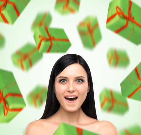 giftwrapped: A portrait of astonishing woman who imagines green gift boxes. Light green background. Stock Photo