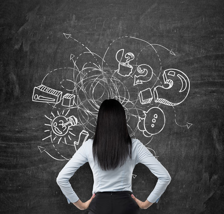 unsolved: Rear view of brunette who is looking at the black chalkboard with drawn sketch of business icons, exclamation and question marks. The concept of brainstorm process.