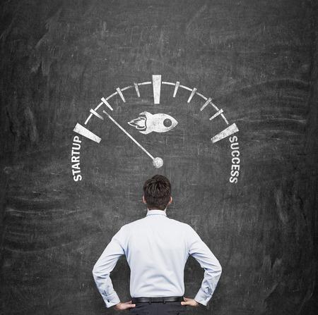 velocímetro: Una vista posterior de un hombre de negocios que está buscando en la escala de desarrollo una puesta en marcha del proyecto de lanzar al éxito. Pizarrón negro en el fondo.