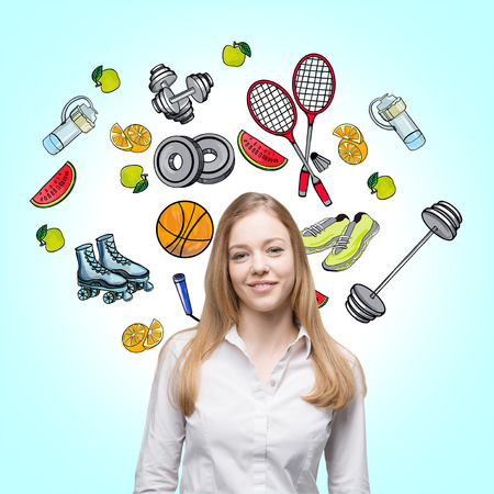 make a choice: A beautiful lady who is trying to make a choice in favour of a certain sport activity. Colourful sport icons are drawn on the light blue background. A concept of a healthy lifestyle. Stock Photo
