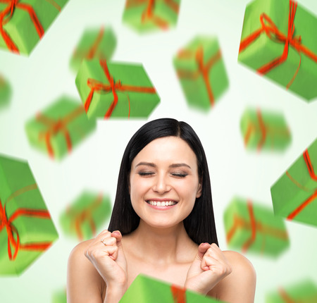 giftwrapped: A portrait of dreaming woman with closed eyes who is imagining green gift boxes. Light green background.