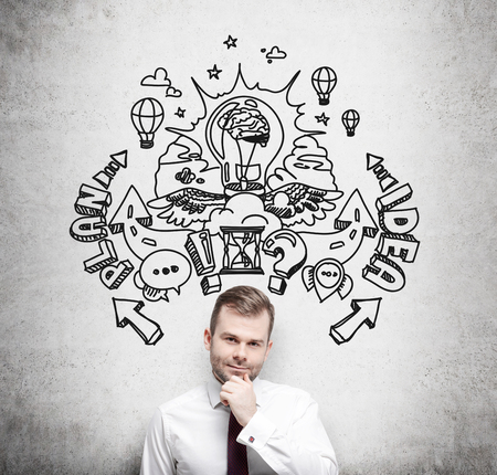 innovating: A handsome young professional is forecasting a building of a business plan for business development. Business plan sketch is drawn on the concrete wall behind the person. Stock Photo