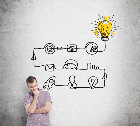 new idea: A young handsome man is thinking about the process of developing a new idea. A flowchart is drawn on the concrete wall with different stages of development. A concept of a brainstorm.