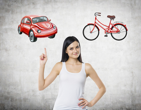 disadvantages: A beautiful woman is trying to chose the most suitable way for travelling or commuting. Her choice is a car. Two sketches of a car and a bicycle are drawn on the concrete wall. Stock Photo