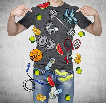 icono deportes: Un hombre en una buena forma f�sica est� se�alando los dedos en los coloridos iconos del deporte. Fondo concreto. un concepto de un estilo de vida saludable.