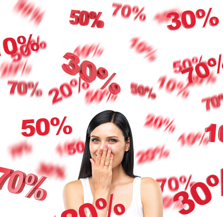 A portrait of a happy brunette lady in a white tank top who is dreaming about discounts. Red percentage marks are flying around the lady on white background.