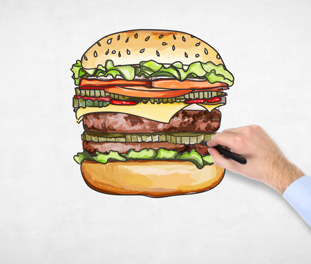 yearning: A mans hand is drawing a colourful burger. A concept of fast food. A concrete background. Stock Photo