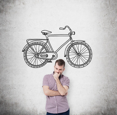 affordable: A person in casual clothes is thinking about affordable or environmental friendly ways of travelling. A sketch of bicycle is drawn on the concrete wall.