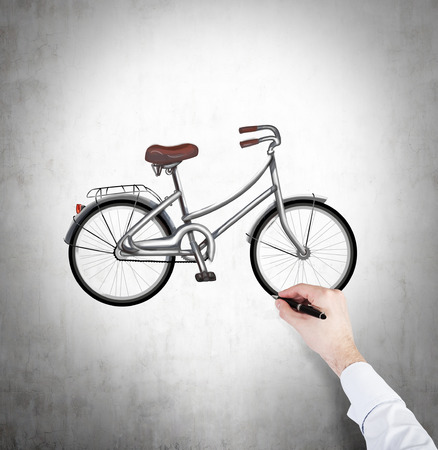 nonpolluting: A hand in formal white shirt is drawing a colourful sketch of bicycle on the concrete wall. Stock Photo