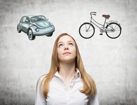 feasibility: A beautiful woman is trying to chose the most suitable way for travelling or commuting. Two sketches of a car and a bicycle are drawn on the concrete wall.