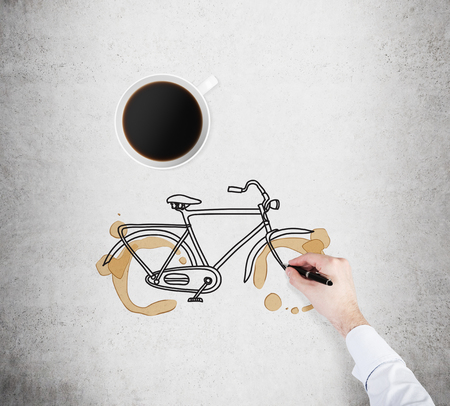 nonpolluting: Top view of a cup of coffee and a drawing process of a bicycle on the concrete surface. A hand in formal white shirt with a pen. Stock Photo