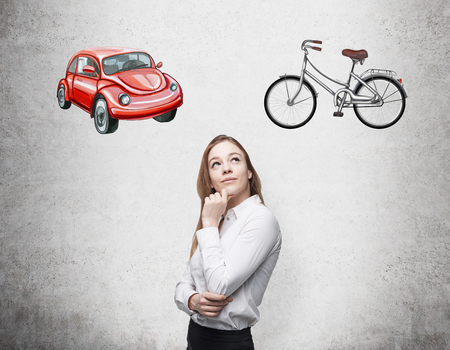 disadvantages: A beautiful woman is trying to chose the most suitable way for travelling or commuting. Two sketches of a car and a bicycle are drawn on the concrete wall.