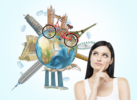 ünlü yer: A brunette woman is dreaming about travelling. The globe with the most famous places in the world. A model of bicycle crosses of the globe.