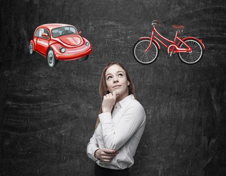 disadvantages: A beautiful woman is trying to chose the most suitable way for travelling or commuting. Two sketches of a car and a bicycle are drawn on the black chalkboard background.