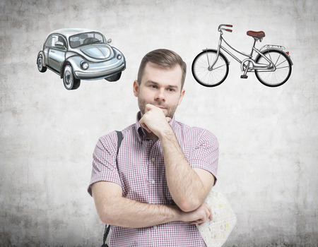 disadvantages: A handsome man in casual shirt is trying to chose the most suitable way for travelling or commuting. Two sketches of a car and a bicycle are drawn on the concrete wall.
