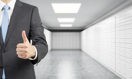 Een privé-manger van een bank met duim omhoog staat in een kamer met kluisjes. Een concept van het opslaan van belangrijke documenten of waardevolle spullen in een veilige omgeving.