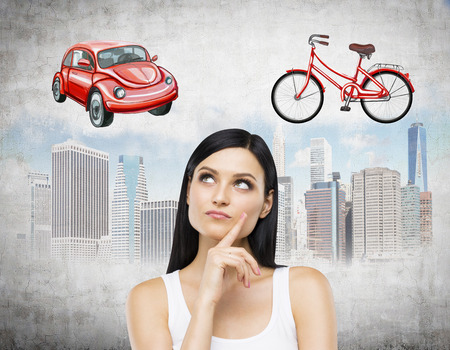 disadvantages: A brunette lady is trying to chose the most suitable way for travelling or commuting in the city. Sketches of a car, a bicycle and New York city are on the concrete background.