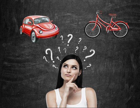 chose: A beautiful brunette woman is trying to chose the most suitable way for travelling or commuting. Two sketches of a car and a bicycle are drawn on the black chalkboard.