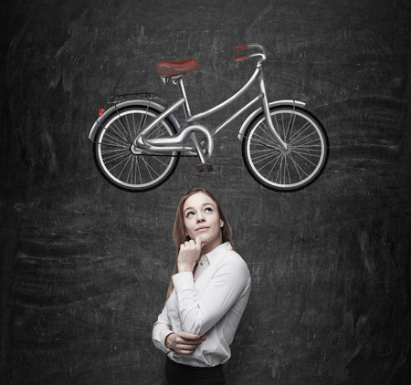 nonpolluting: A beautiful girl in formal clothes is dreaming about a new bicycle. A sketch of a bicycle is drawn on the black chalkboard.