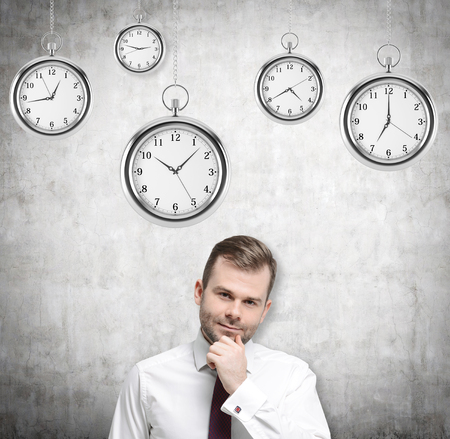 streamlining: A portrait of a thinking handsome businessman who is holding his own chin. Several models of pocket watches are hovering in the air. A concept of a value of time in business. Concrete background. Stock Photo