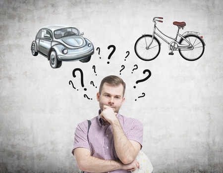 chose: A handsome man is trying to chose the most suitable way for travelling or commuting. Two sketches of a car and a bicycle are drawn on the concrete wall. Question marks are around mans head.