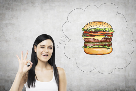 delicious food: A brunette woman is thinking about burger. A fast food concept. Concrete background.