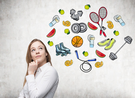 thinking woman: Dreaming beautiful lady is thinking about her choice of sport activity. Colourful sport icons are drawn on the concrete wall. A concept of a healthy lifestyle. Stock Photo