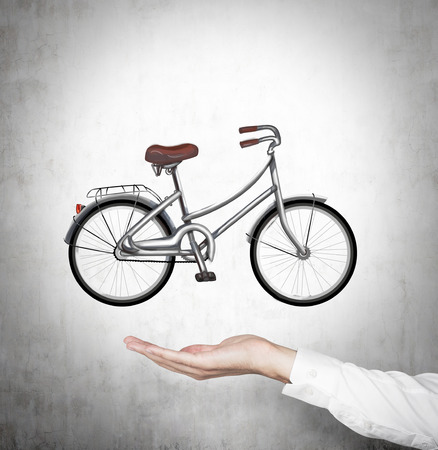 nonpolluting: A hand in formal shirt holds a bicycle which is drawn on the concrete wall.